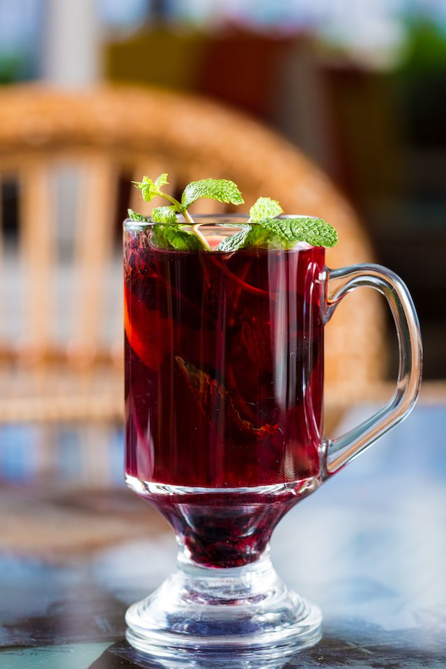 Blackberry tea in a glass cup. Decorated with mint leaves