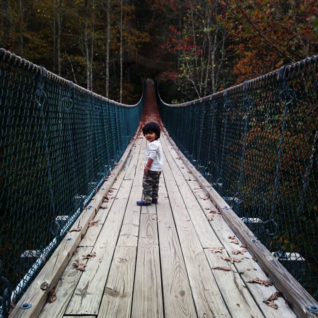 Cute kid walking across the swinging bridge at Foxfire Mountain Adventure Park