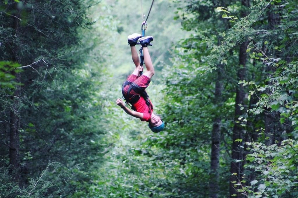 Person zip lining upside down at Foxfire Mountain Adventure Park