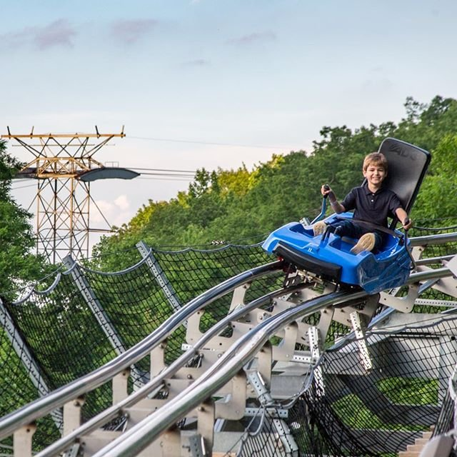 Child smiling while riding the Ski Mountain Coaster at Ober Gatlinburg