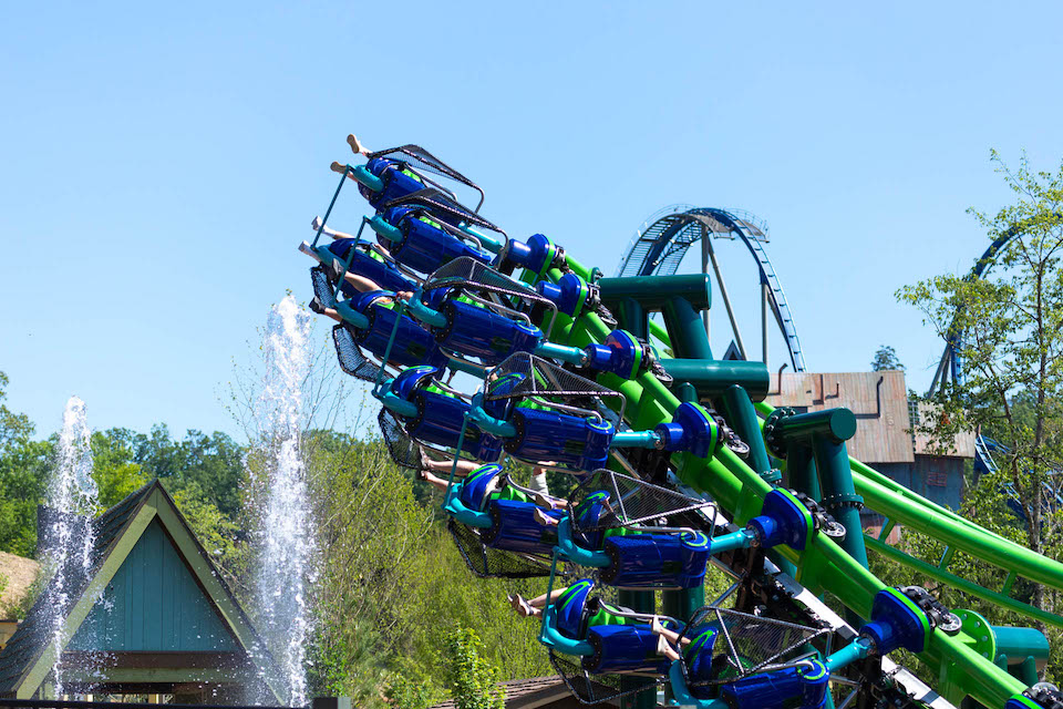 Riders on the Dragonflier Coaster going around an inverted curve.