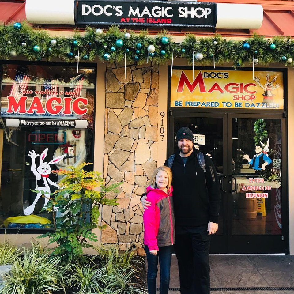 Man and Child pose outside of Doc's Magic Shop at the Island