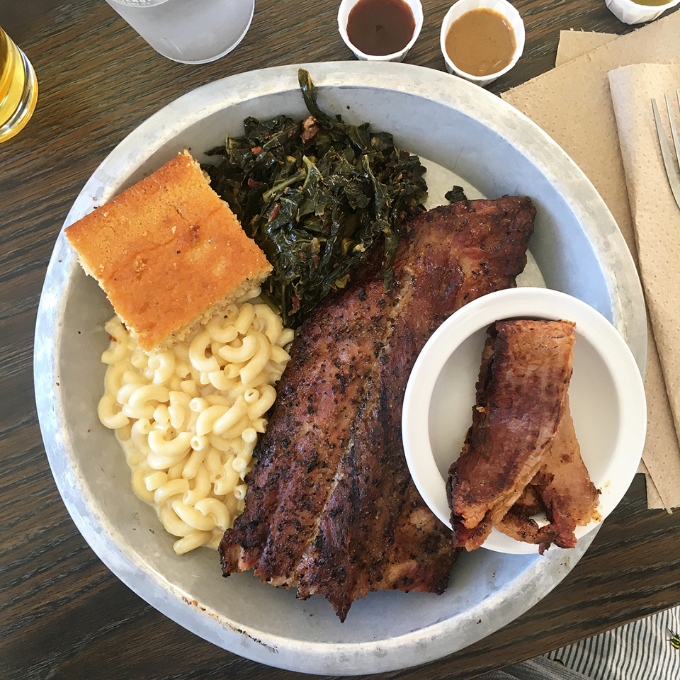 Plate with dry rub ribs, mac and cheese, turnip greens and corn bread