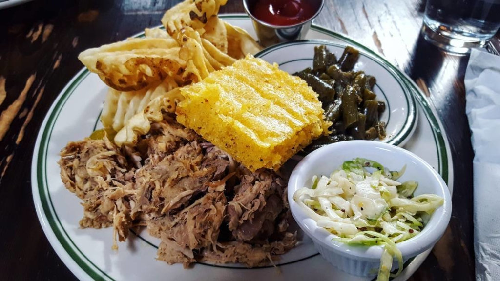 Bbq, cornbread, waffle fries, cole slaw and green beens on a plate.