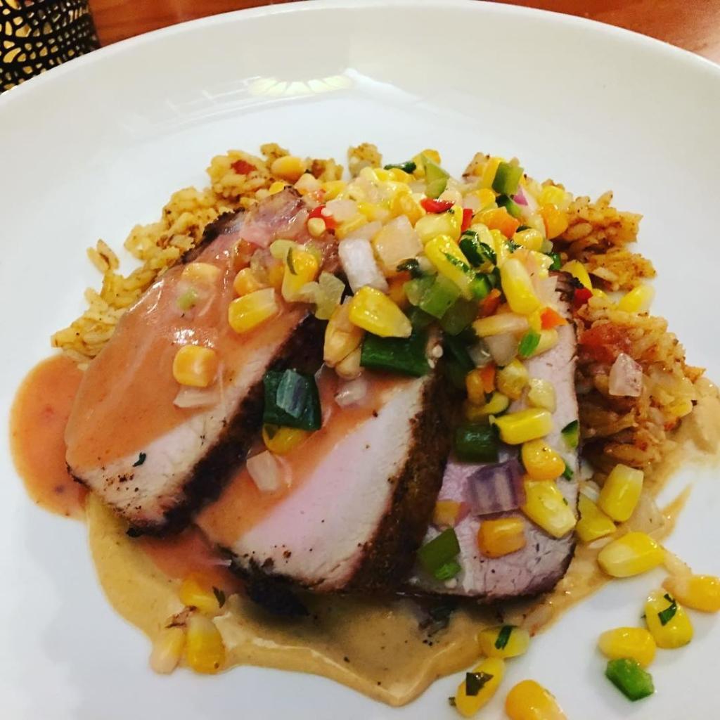 Pork tenderloin on a bed of rice on white plate.