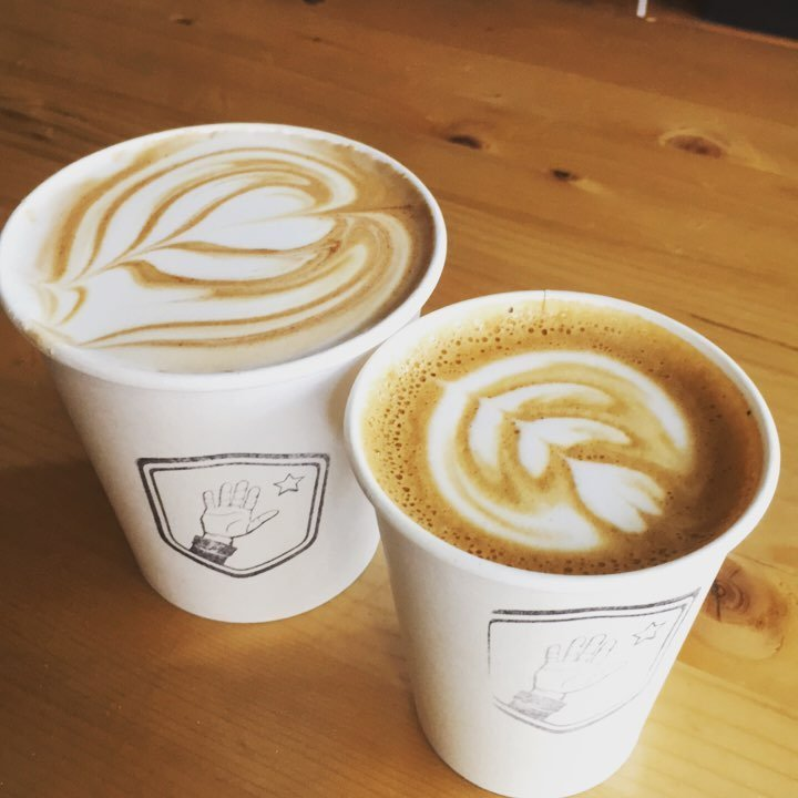 Two lattes side by side with latte art.