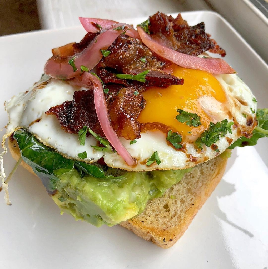 Toast on plate topped with avocado, greens, sunny side up egg, bacon and pickled onions