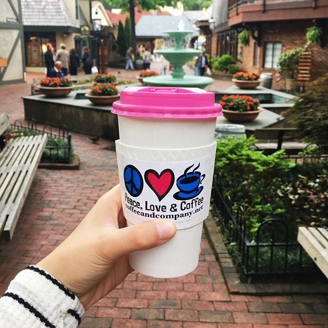 Girl holding coffee cup in front of village in Gatlinburg