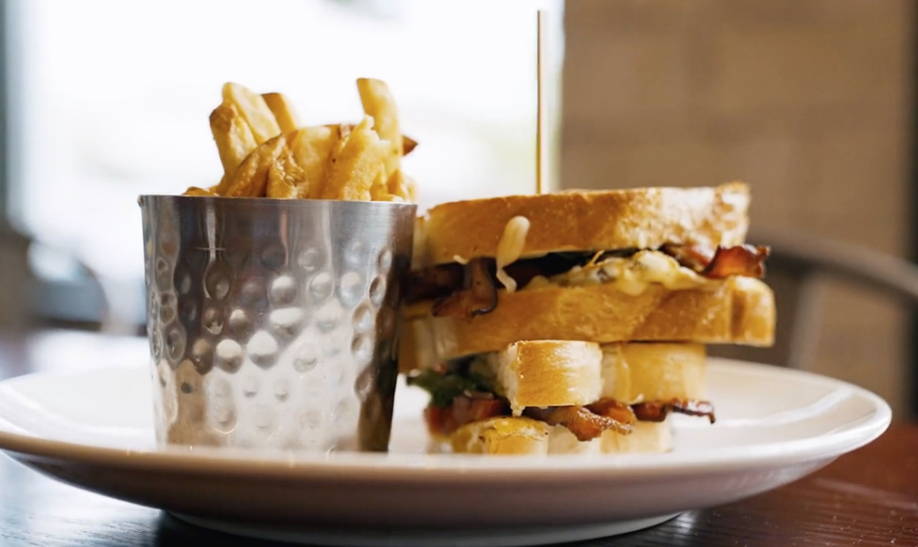 bacon and egg sandwich and fries on a plate.