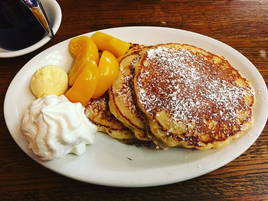 3 pancakes on plate with peaches and whipped cream
