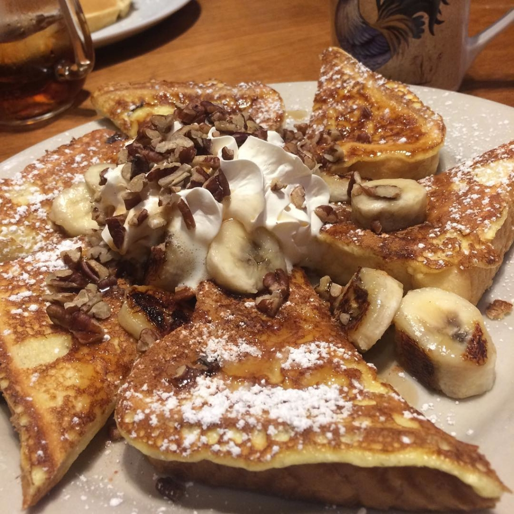 french toast on plate topped with whipped cream, bananas and walnuts
