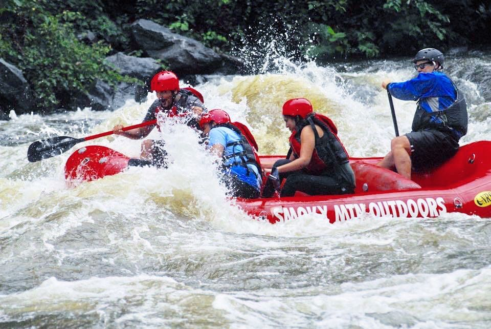 people navigating a large wave while white water rafting