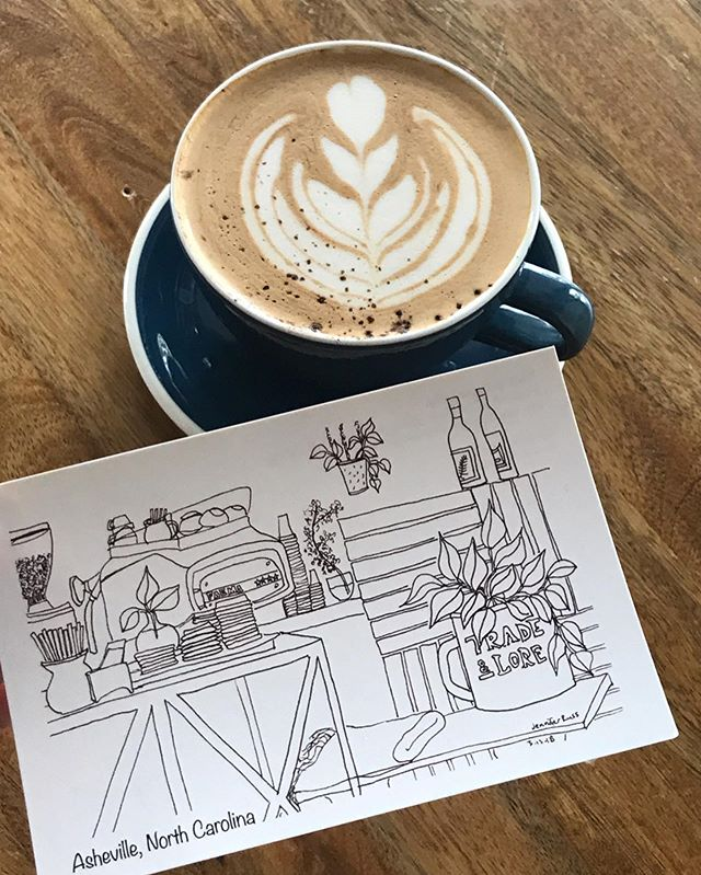 latte in a mug with a drawing of coffee shop interior placed beside