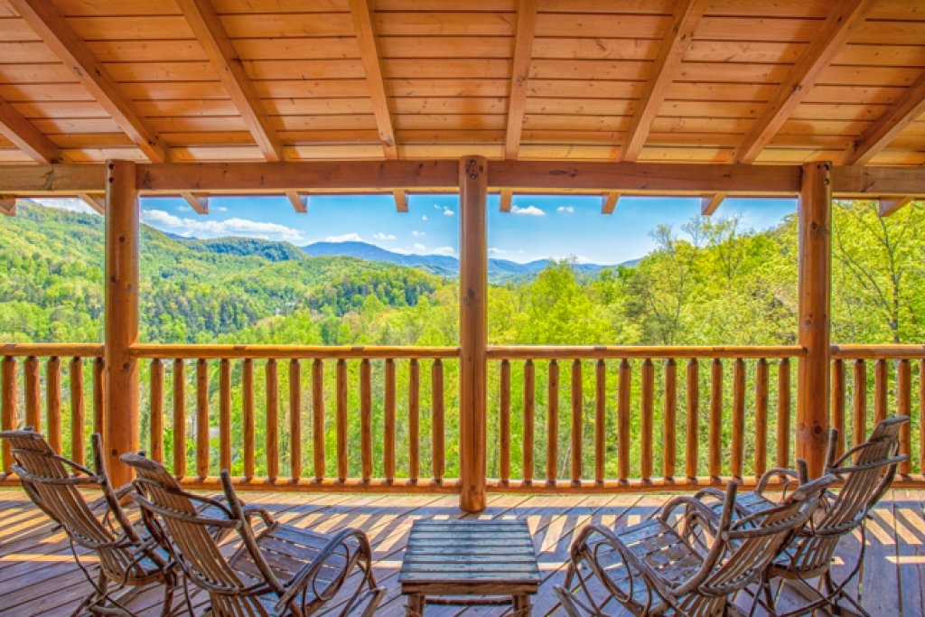4 rocking chairs on a deck looking out into the mountains