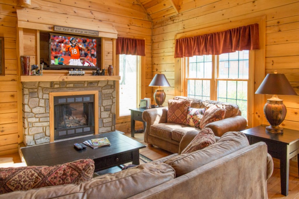 cabin living room with tv over stone fireplace