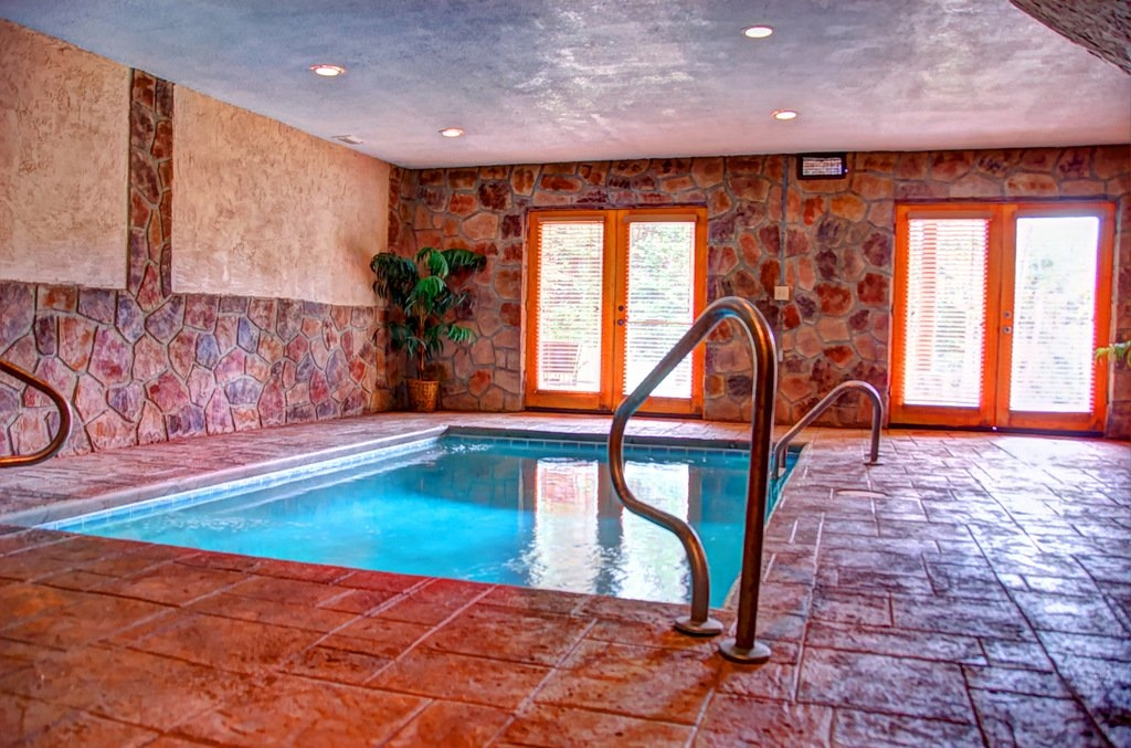 indoor pool area with stone walls and glass doors
