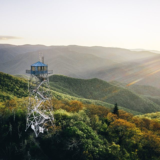 tower in the mountains with sun beaming down