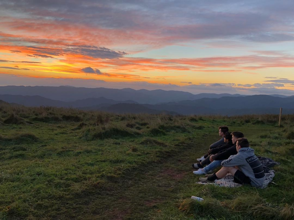 4 young men sitting on a mountain top watching a sunset