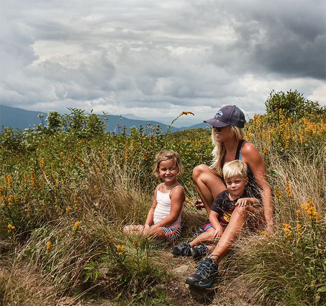 Woman with kids surrounded by flowers and mountain views