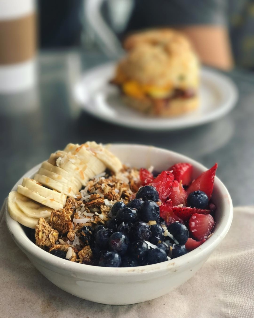 bowl of granola with banana, strawberries and blueberries in foreground and biscuit blurred in background