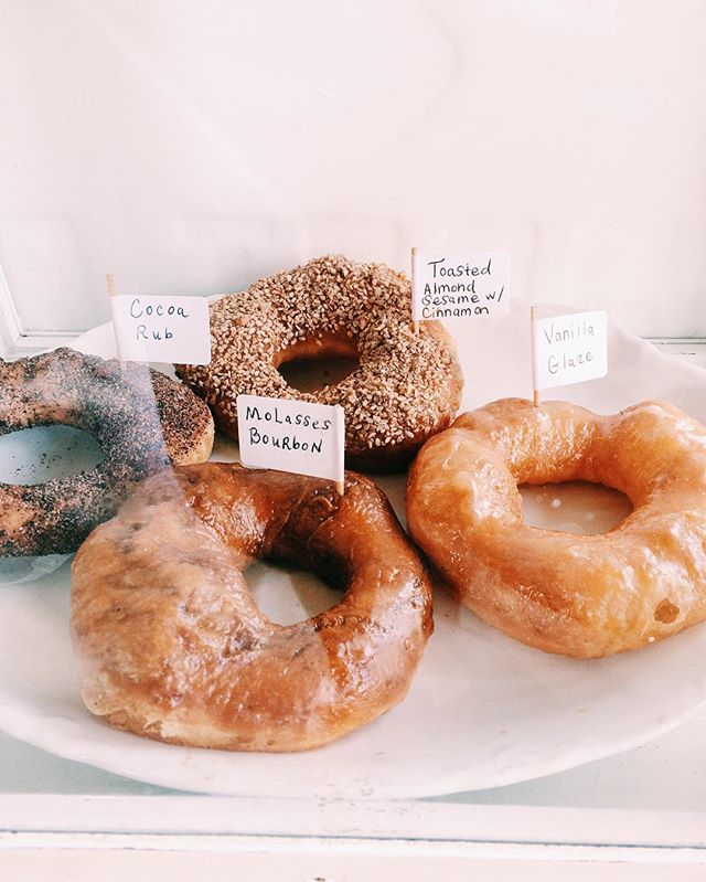 4 doughnuts on white plate with signs describing the flavors