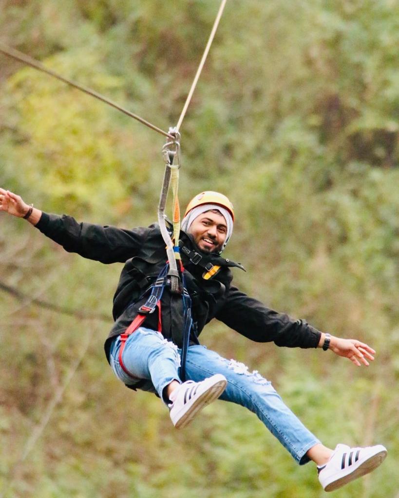 smiling man with beard on zipline