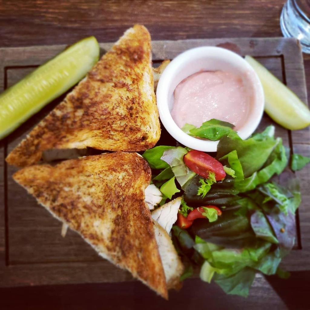 sandwich cut into two triangle pieces next to pickle spears and salad with dipping sauce