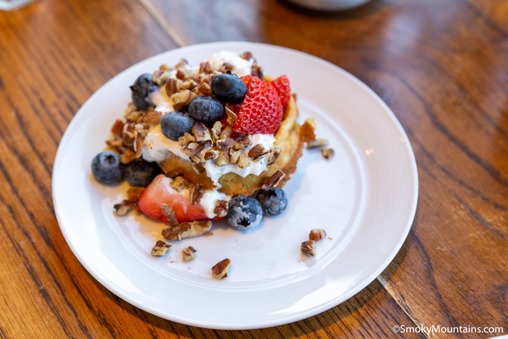 brunch item on white plate with nuts, blueberries, and strawberries on wooden table at blue ridge